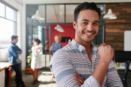Portrét inteligentní kreativní profesionály, na kameru a usmíval se. Šťastné kavkazské muž stojící v kanceláři s kolegy diskutovat v kanceláři.
