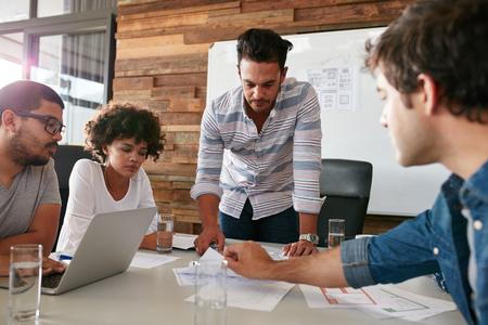 Il giovane discutere di ricerche di mercato con i colleghi in una riunione. Squadra di giovani professionisti che hanno una riunione nella sala conferenze guardando i documenti.