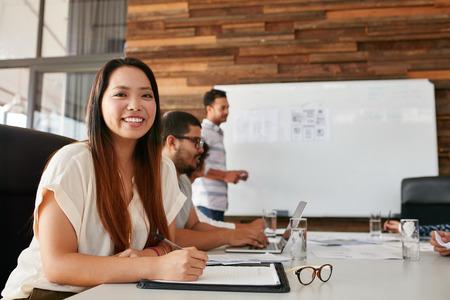 배경에서 동료와 함께 회의 테이블에 앉아 행복 한 젊은 여자의 초상화. 아시아 여자는 비즈니스 프레젠테이션에 앉아있는 동안 카메라를보고 웃 고.