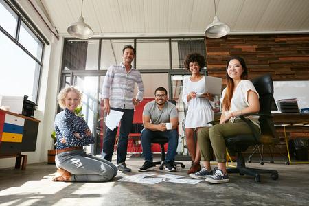 Портрет счастливых молодых людей в заседании, глядя на камеру и улыбается. Молодые дизайнеры работают вместе над творческим проектом. Фото со стока