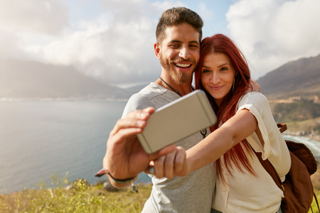 Young couple hiking taking selfie with smart phone. Happy young man and woman taking self portrait with mountain scenery in background. Stock Photo