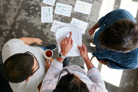 point of view: Top view of hands of three young people discussing financial transactions during a meeting. Man pointing at document while standing with colleagues in office. Business partners discussing financial data at meeting
