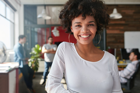 looking at: Portrait of smiling young african businesswoman with people in background. Cheerful young woman standing relaxed in her office, looking at camera and smiling.