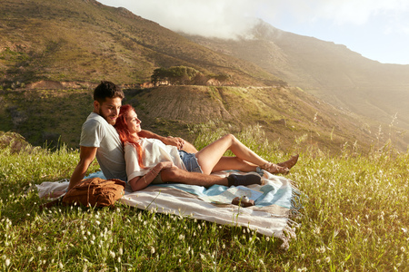 couple nature: Happy young couple on picnic blanket. They are relaxing together on a summer day.