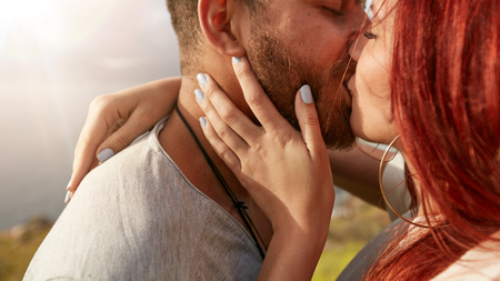 love very: Close up shot of loving young couple kissing outdoors. Man and woman kissing each other romantically looking very much in love. Stock Photo