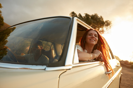 Portrait of happy young woman going on a road trip leaning out of window. Female enjoying travelling in a car with her boyfriend. photo