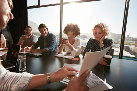 Gros plan des mains du jeune cadre masculine discuter plan d'affaires avec des collègues. Les personnes créatives réunis à la salle de conférence.