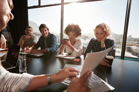 Nahaufnahme der Hände der jungen männlichen Exekutive diskutieren Business-Plan mit den Kollegen. Kreative Menschen im Konferenzraum treffen.