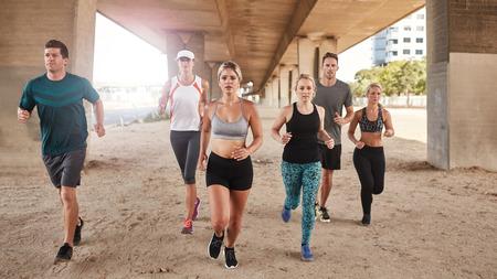 gente corriendo: la gente joven sana que se ejecuta bajo un puente. Grupo de hombres y mujeres jóvenes que hacen el entrenamiento corriente. Foto de archivo