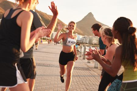 Grupa kibiców dopingujących biegaczy tuż przed metą. Kobieta biegacz kończąc wyścig z jej zespołu brawo jej wysiłki.