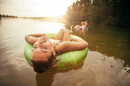Closeup portrait of young woman with her eyes closed relaxing on inflatable ring in lake on a sunny day.