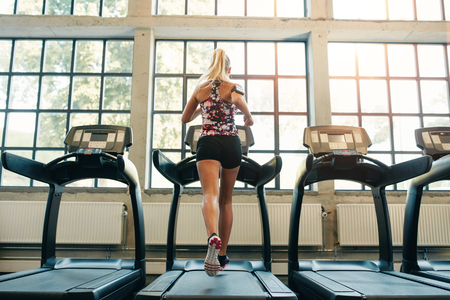 self conscious: Horizontal shot of woman jogging on treadmill at health club. Female working out at a gym running on a treadmill.