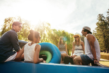 youth group: Group of young friends sitting in the back of a pickup truck with inflatable tubes going on a summer holidays on a sunny day. Stock Photo