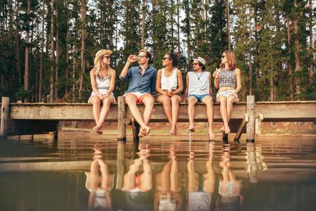 Jongeren zitten op de rand van een steiger met hun opknoping naar het water. Groep jonge vrienden opknoping uit bij het meer. Stockfoto