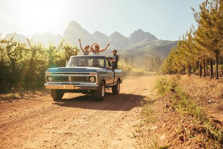 persona viajando: Amigos que se divierten en la parte trasera abierta de un camión de cosecha en un día de verano en el campo. Los hombres jóvenes y una mujer disfrutando de un viaje por carretera.