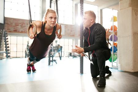 muscle training: Junge Frau ist in einem modernen Gymnastikübungen mit Hilfe von einem persönlichen Trainer zu tun. Frauen arbeiten an den gymnastischen Ringen. Lizenzfreie Bilder