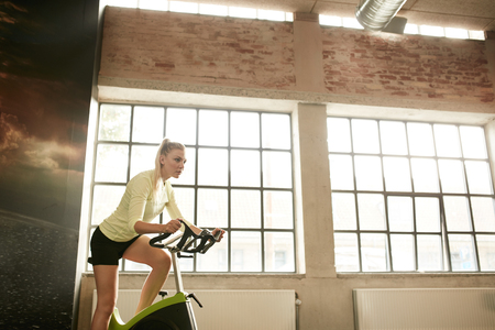 self conscious: Fitness woman exercising on a spinning cycle in gym. Caucasian young female athlete doing fitness training on a stationary bike. Stock Photo