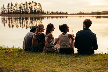 man rear view: Rear view portrait of group of young friends relaxing by a lake. Young people sitting together by a lake. Stock Photo