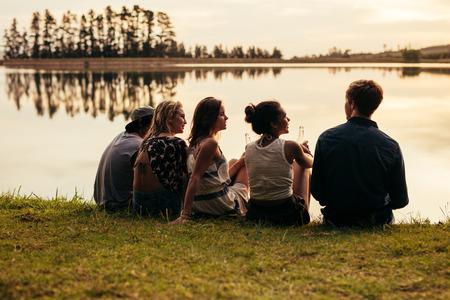 personas hablando: Vista trasera retrato de grupo de jóvenes amigos que se relajan por un lago. Los jóvenes sentados juntos por un lago.