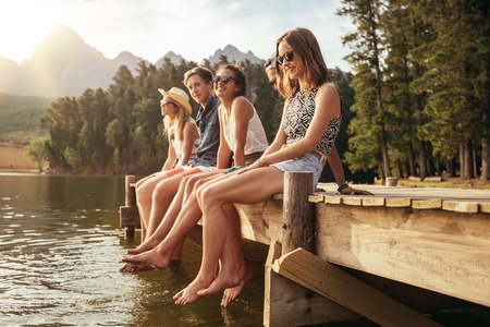 Portrait of group of young people sitting on the edge of a pier, outdoors in nature. Friends enjoying a day at the lake. Stock Photo