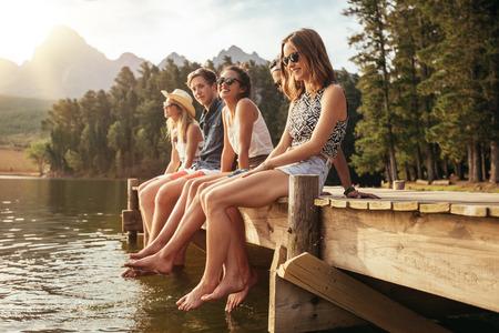 personas sentadas: Retrato de grupo de jóvenes que se sientan en el borde de un muelle, al aire libre en la naturaleza. Amigos disfrutando de un día en el lago.
