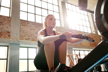 gym workout: Young woman using rowing machine in the gym. Caucasian female doing cardio workout in fitness club. Stock Photo