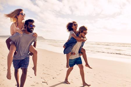 Twee mooie jonge paren lopen aan het strand, met mannen die hun vrouwen op hun rug. Paren meeliften op de kust. Het hebben van pret op het strand vakantie. Stockfoto