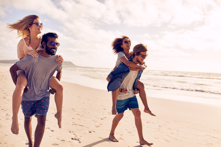 Two beautiful young couples walking by the beach, with men carrying their women on their back. Couples piggybacking on sea shore. Having fun on beach vacation. Standard-Bild
