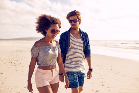 Portrait of young couple walking on the beach. Young man and woman strolling on the shoreline during the summertime.