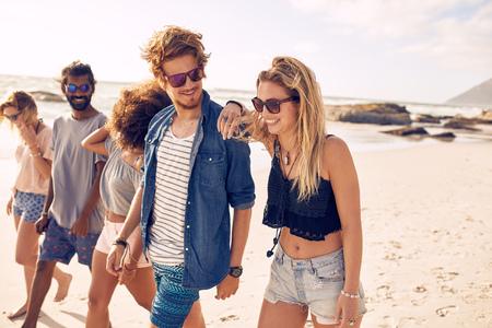 Zróżnicowana grupa młodych przyjaciół mających na spacer po plaży. Młodzi ludzie patrząc szczęśliwy na wakacjach. Młodzi mężczyźni i kobiety chodzenia na wybrzeżu.