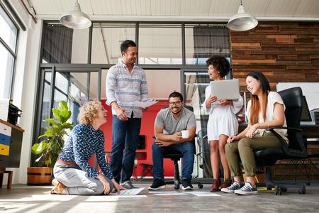 Группа творческих людей обсуждают новый проект. Женщина сидит с документами, уложенных на полу и улыбается, имея встречу в современном офисе. Фото со стока
