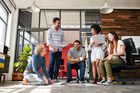 personas sentadas: Grupo de personas creativas que discuten nuevo proyecto. Mujer que se sienta con los documentos establecidos en el piso y sonriendo mientras que tiene una reuni�n en la oficina moderna.
