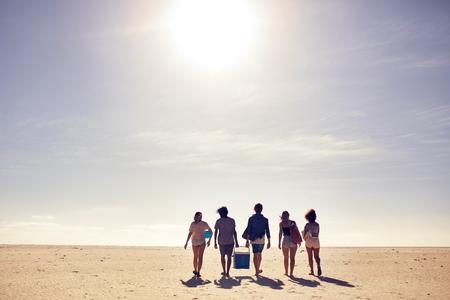 年輕人背著保溫箱走在沙灘上的後視圖肖像。尋找黨的一個點。上海灘度假的朋友,在炎熱的夏天的一天。 版權商用圖片