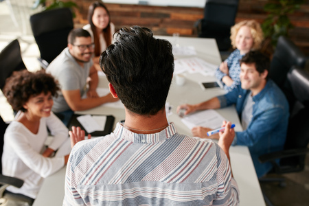 Rear view portrait of man explaining business ideas to colleagues during a meeting in conference room. Young people meeting in boardroom.