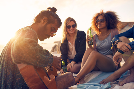 Hipster playing guitar for friends at the beach. Group of young people drinking beer and listening to music. Foto de archivo