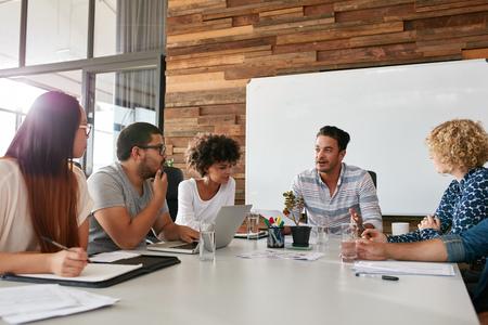 Tiro de um grupo de profissionais jovens que têm uma reunião na sala de reuniões. Os trabalhadores de escritório discutem o novo plano de negócios juntos em uma sala de conferências.