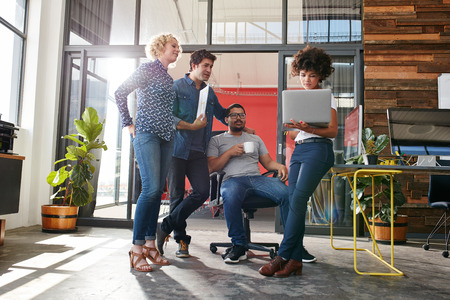 jovenes empresarios: Grupo multirracial de diseñadores se encuentran en oficina que discute el trabajo moderno. Los jóvenes empresarios que tienen una reunión para el nuevo proyecto creativo.