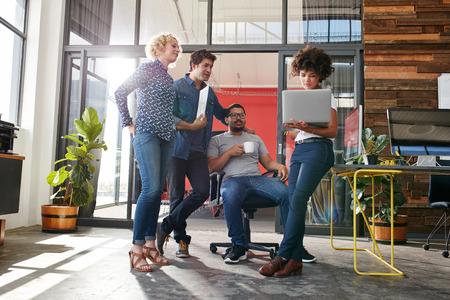 Multiraciale groep ontwerpers bijeen in moderne kantoor bespreken werken. Jonge ondernemers met een bijeenkomst voor nieuwe creatieve project.