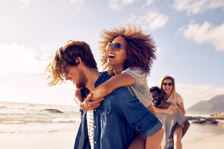 Grupo de amigos caminando por la playa, con los hombres da a cuestas paseo a amigas. Feliz jóvenes amigos disfrutando de un día en la playa.