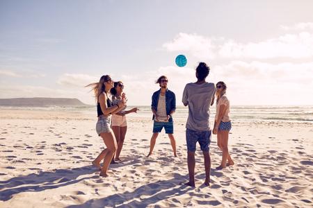 ビーチでボールで遊ぶ若者のグループ。若い友人は、砂浜のビーチで夏休みを楽しんでいます。