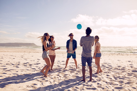 Group of young people playing with ball at the beach. Young friends enjoying summer holidays on a sandy beach.