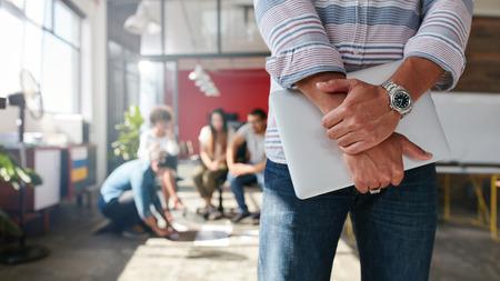 image recadrée de l'homme debout devant avec des collègues de discuter en arrière-plan, se concentrer sur les mains d'un concepteur tenant ordinateur mâle ordinateur portable.