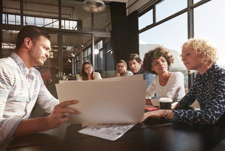 Gelukkig en succesvol team van collega's bij elkaar zitten uit te werken business plannen