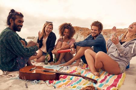 Группа молодых друзей, празднование на пляжной вечеринке вместе. Молодые люди, имеющие Нового года на морском побережье.