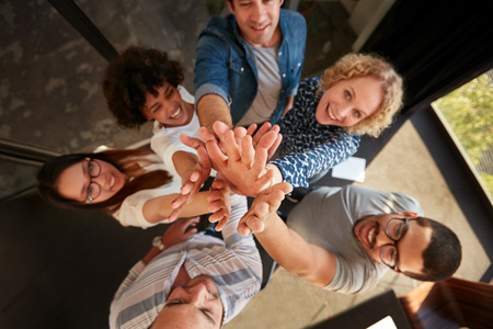 Top view of successful team of professionals high fiving and looking at camera smiling. Men and women making a pile of hands in office.