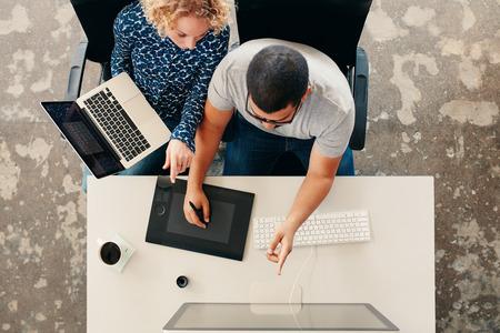hombres trabajando: Vista superior de jóvenes diseñadores gráficos que trabajan juntos en la oficina. El uso de la tableta gráfica digitalizada, la pluma digital y el ordenador de sobremesa. El hombre que muestra su trabajo en el monitor a la mujer con un ordenador portátil. Foto de archivo