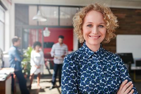 笑顔若い女性デザイナー立っている彼女のオフィスで、バック グラウンドでいくつかの同僚との肖像画。 写真素材