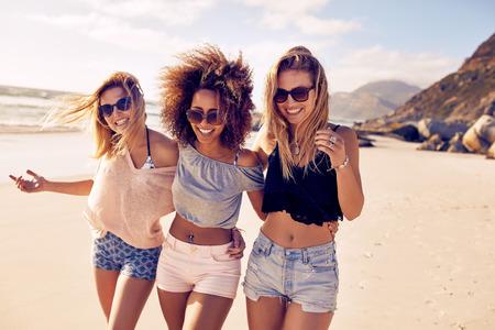 Portret trzech młodych przyjaciół żeński chodzenia na brzegu morza, patrząc na kamery śmiechem. Wielorasowe młode kobiety spacery wzdłuż plaży.