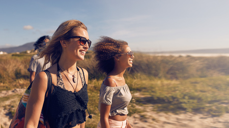 travel woman: Portrait of smiling young women going on the beach. Female friends on sea shore on summer day, beach vacation.