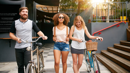 friends fun: Three young people walking down the street with their bicycles. Male and female friends on road with their bike. Stock Photo